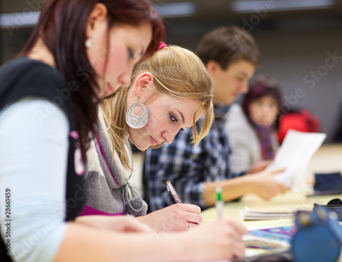 pretty female college student sitting in a classroom full of stu