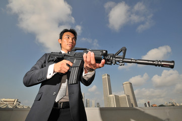 Asian Chinese Man carrying a High Powered Rifle