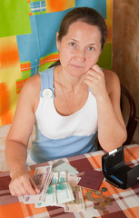 sad mature woman with money