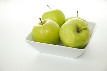 Green Apples in a White Bowl on White Background