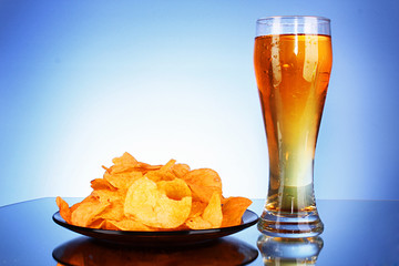 Beer and potato chips on blue background