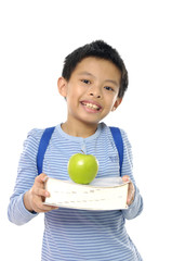 kid holding apples on book  with a smile