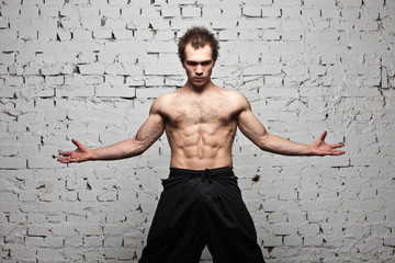 Strong muscular man stay at evil state white brick wall