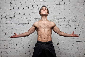 Strong muscular man stay like fly  at white brick wall
