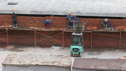 Workers build a wall of a brick, a building site