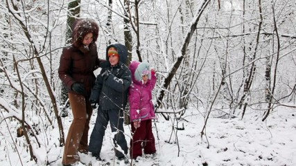Mother with children in snow forest