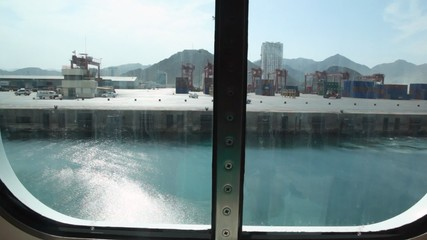 view of seaport through porthole of sailing ship