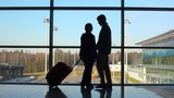 silhouettes of couple stands against window at airport