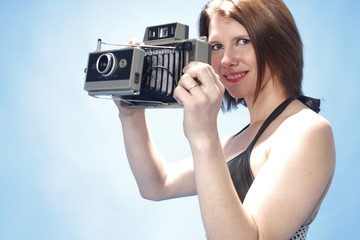 Sexy woman with an instant camera