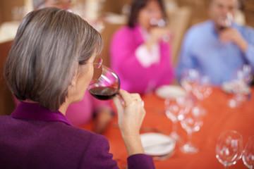 ältere dame trinkt rotwein im restaurant