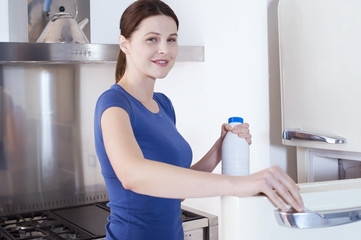 woman opening the refrigerator with milk bottle