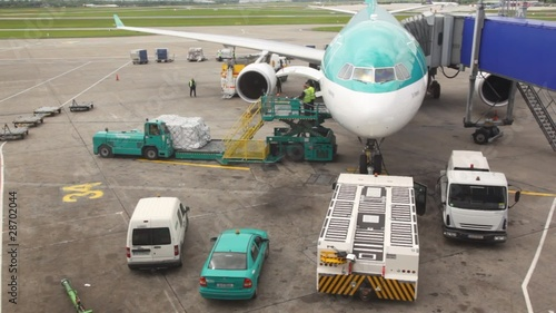 plane standing at airstrip is loaded with goods by workers
