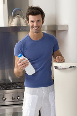 man in the kitchen with a bottle of milk