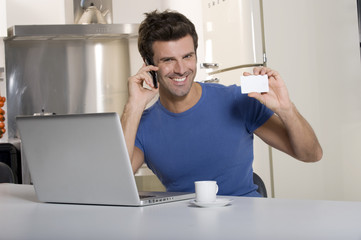 man in the kitchen with laptop and mobile