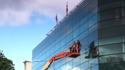 workers standing on crane washing glass building with flags