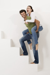 man climbing the stairs with woman on his shoulders