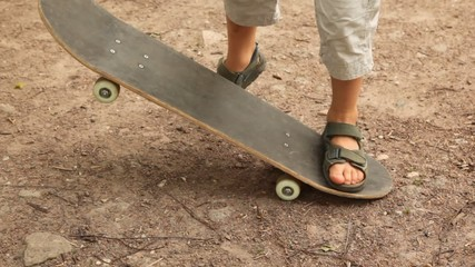 boy studies to go for a drive on a skateboard