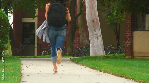 Young woman at school running to class