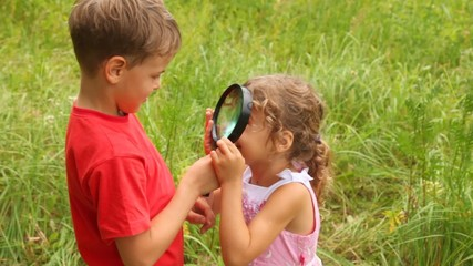 sister is looking at her brother through the lens