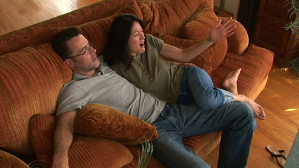 Young couple on couch using remote to watch TV