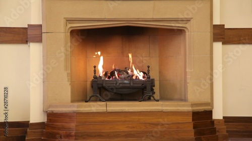 flame in fireplace in middle of brown room