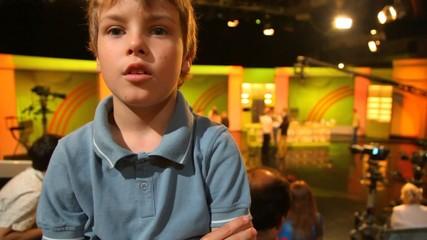 boy standing in big TV studio with spectators