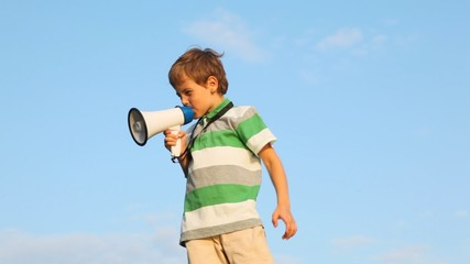 boy standing against sky, talking through megaphone