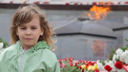 girl standing against eternal fire on monument