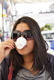 Young asian woman drinking an expresso in Italy