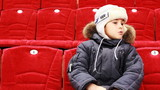 boy sits in armchair, attentively watch hockey match
