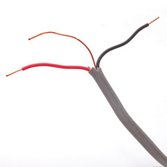 Close up of electric wire on a plain white background.