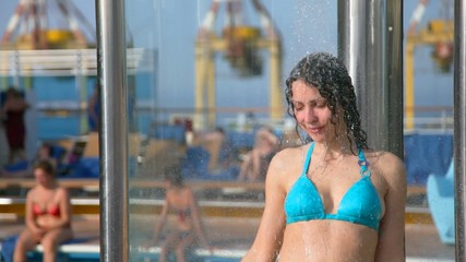 woman taking a shower near outdoor swimming pool