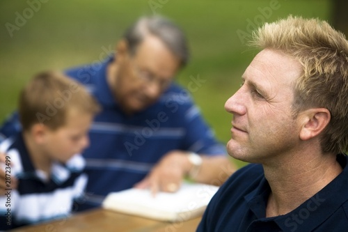 Man Reflecting While His Family Is Reading