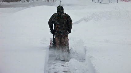 Man pushes snow blower away in blizzard