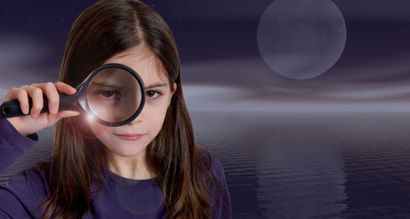 Girl holding magnifying glass on moonlight