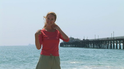 Young woman at the beach with pier in background