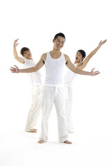 Group of three people in white cloths in a gym doing gymnastics