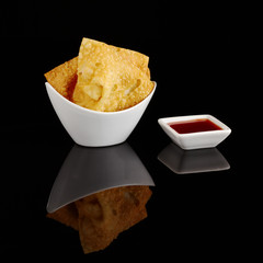 Chinese fried wantan chips in a white bowl on black