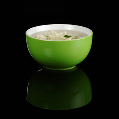 Chinese wantan soup in a green bowl on black