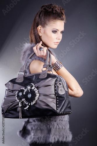 Beauty Brünette blickt cool mit Handtasche in die Ferne, hoch