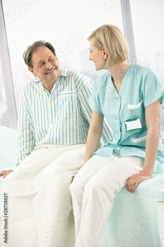 Nurse and patient sitting on bed