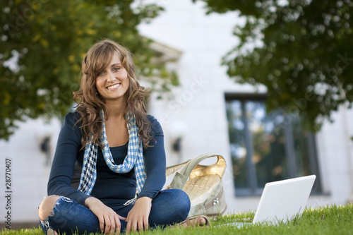 Female Student Portrait sitting outside an academic building