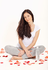 Young beautiful woman sitting in lotus pose with bottle of water
