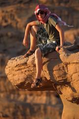 joven adolescente sentado en el desierto