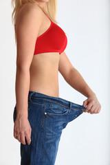 Frau nach Diät mit alter Jeans