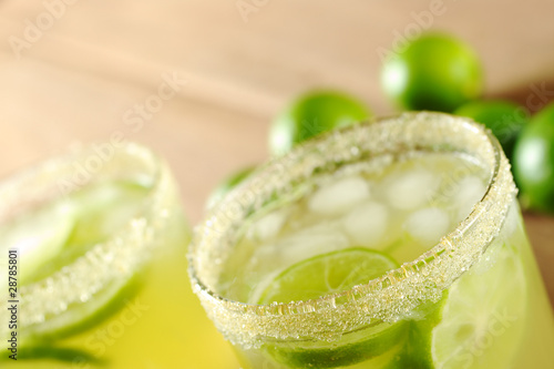 Fresh lemonade of green limes in sugar-rimmed glasses