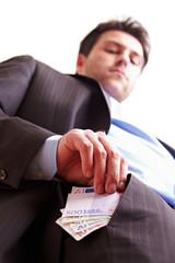 Manager steckt Geld in Hosentasche