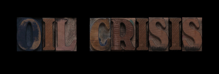 the words oil crisis in old letterpress wood type