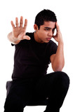 young latin man, pensive, with his hand in stop signal