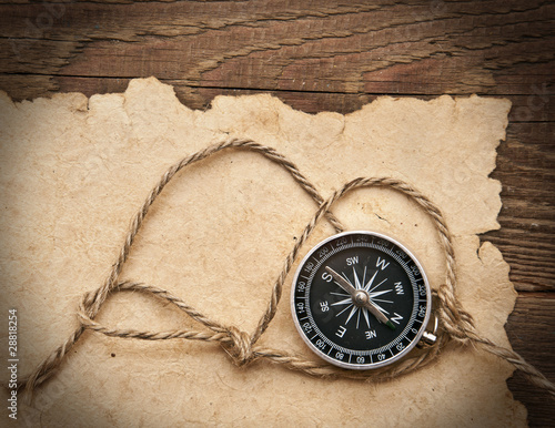 compass, rope and old paper on border wood background